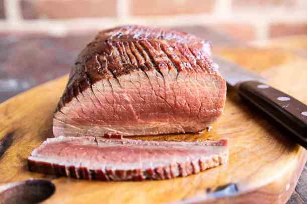 slicing a smoked venison leg roast