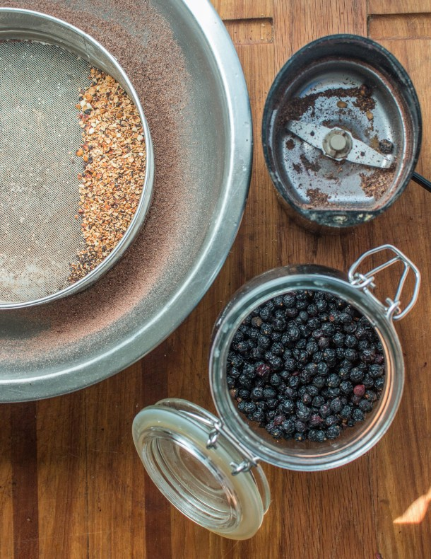 Grinding dried wild chokecherries into flour for bird cherry cake