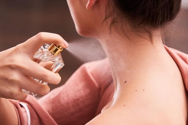 alergie la parfum - pulverizare parfum din abundenta pe gatul unei femei