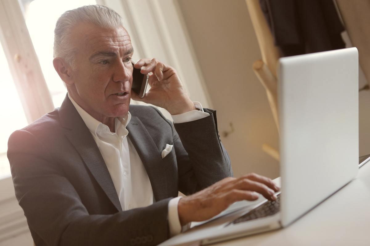 Señor teletrabajando mientras habla por teléfono