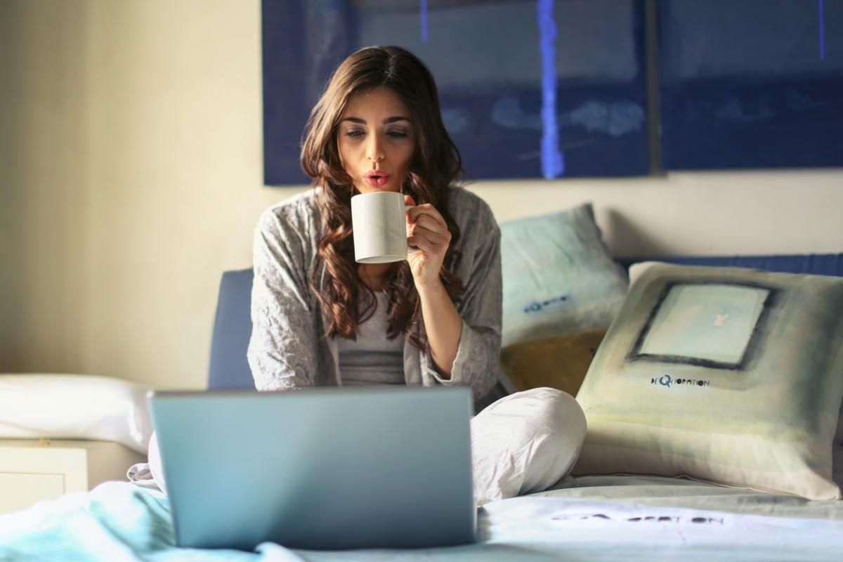 chica sentada sobre una cama con un portátil bebiendo de una taza