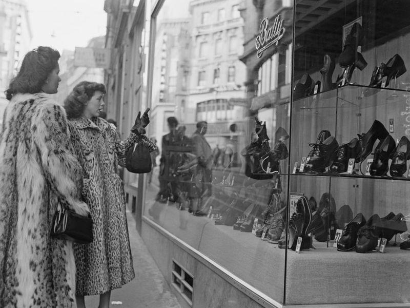 Dos jóvenes admiran el escaparate de una zapatería. Foto: Archivio Cameraphoto Epoche/Getty Images