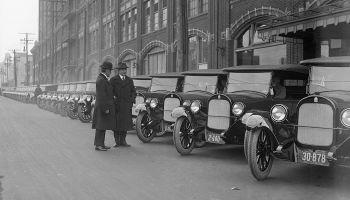 Fabricantes de coches de los años 20 inspeccionan sus vehículos.