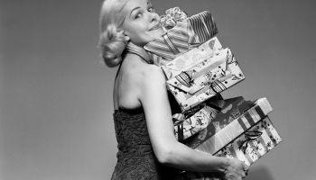 Una mujer sostiene una montaña de regalos mientras mira a la cámara. Foto: Debrocke/ClassicStock/Getty Images
