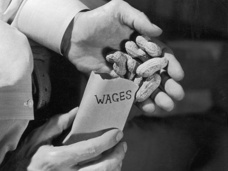 Foto tomada en torno a 1955. Primer plano de una mano de un hombre llenando de cacahuetes un sobre en el que pone salario. Foto: Harold M. Lambert/Lambert (Getty Images)