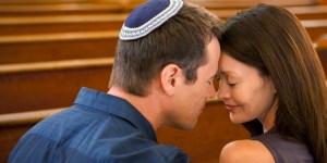 Man in yarmulke praying with girlfriend