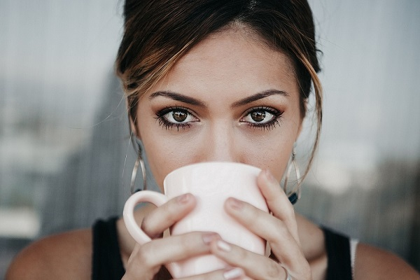 Coffee loving woman drinking coffee from a white cup