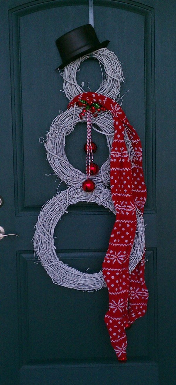 DIY Twigs Snowman Wreath. This creative snowman wreath is made with twigs, ribbons and Christmas balls, then dress it up with a hat and scarf. It looks so great on your front door.