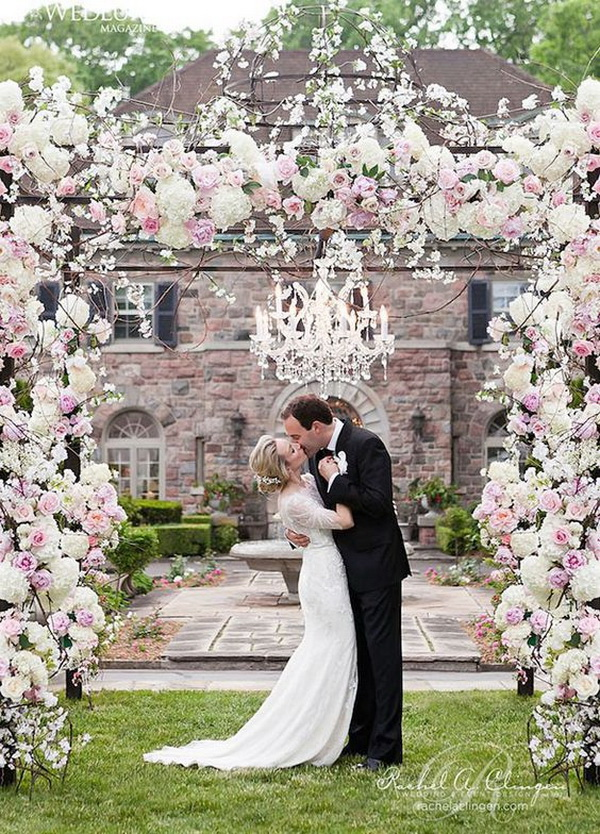 Wedding Arch Overflowing with Roses, Hydrangeas, Peonies and Accented with a Hanging Crystal Chandelier. What a beautiful wedding arch decoration idea! Love it!