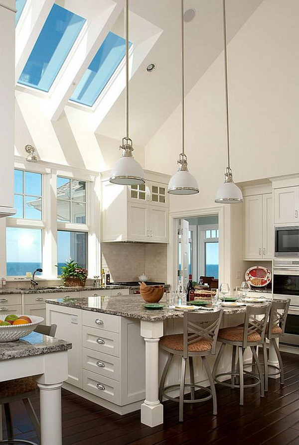 What a beautiful and large white kitchen with white cabinets, dark wood floors, vaulted ceilings with skylights, granite countertops, large kitchen island. More via https://forcreativejuice.com/elegant-white-kitchen-interior-designs/