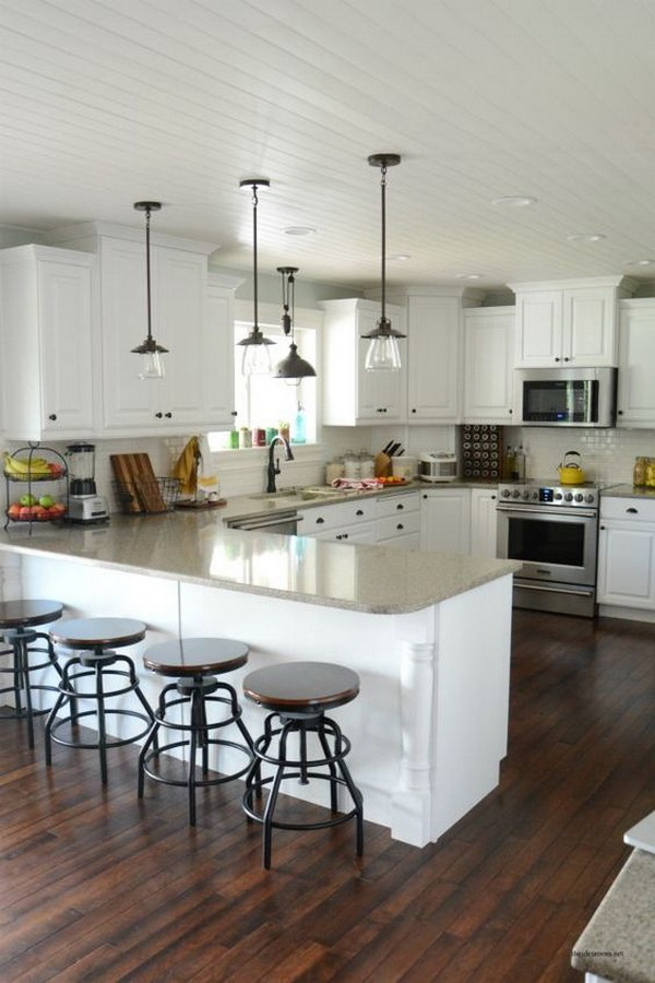 A stunning white kitchen complete with updated pendant lights and smudge-proof Frigidaire appliances. More via https://forcreativejuice.com/elegant-white-kitchen-interior-designs/