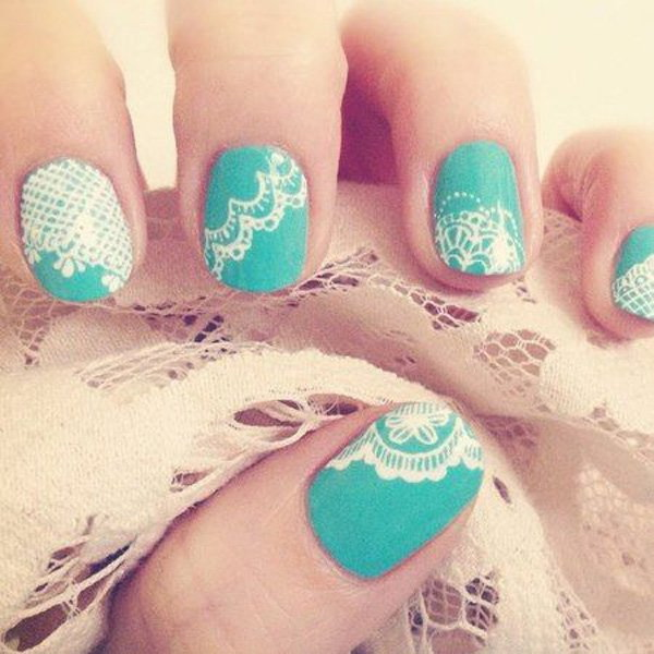 Intricate white lace on turquoise nail polish.