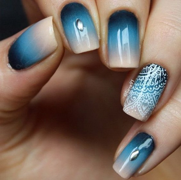 Ombre blue nail design with white lace details on top.
