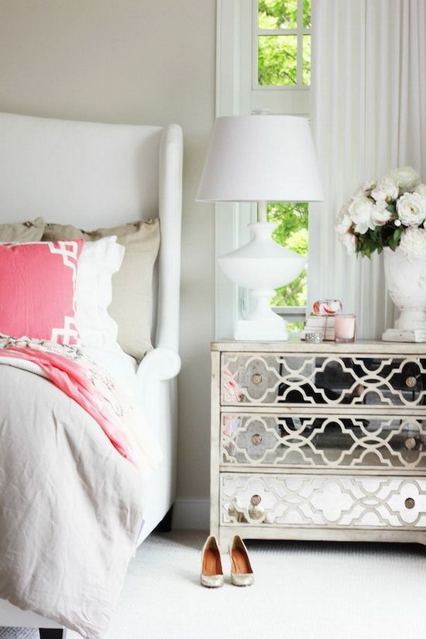 Teen girls' bedroom with coral decor pillow and mirrored dresser.