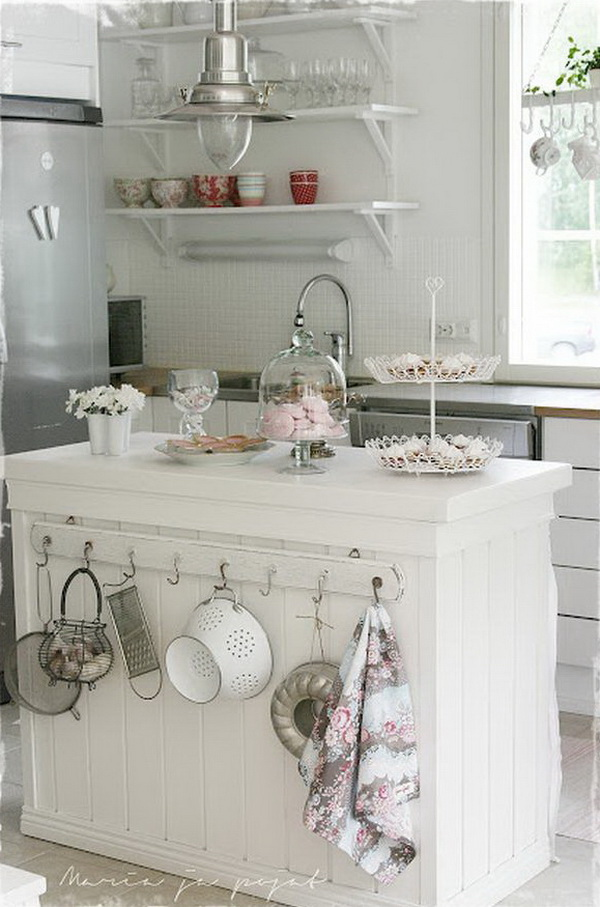 White Shabby Chic Kitchen Island with Slightly Mismatched Hooks on One Side.