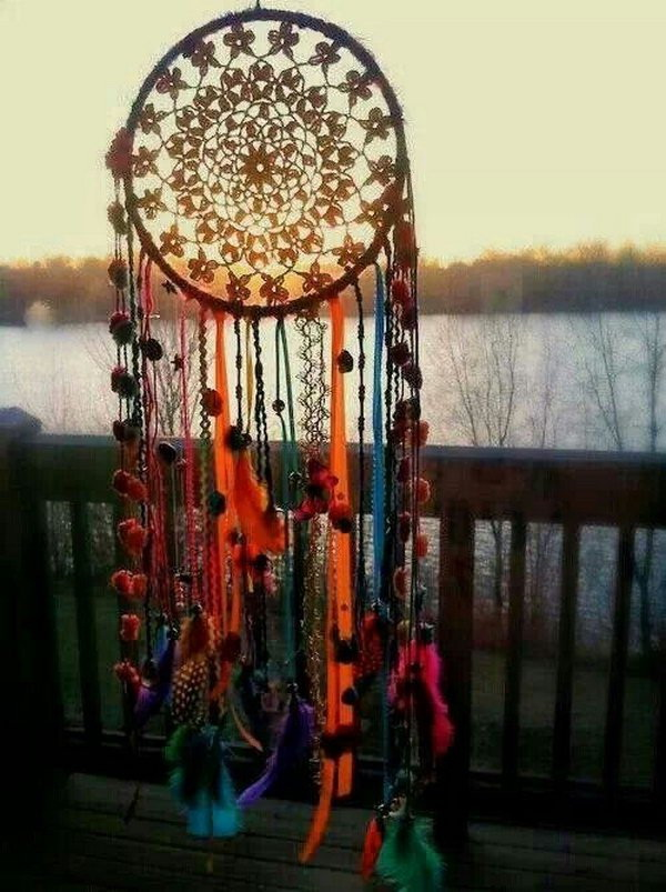A colorful dream catcher that is made out of feathers and fluffy pom pom in  various colors. It looks so lively and vibrant in a boho style.