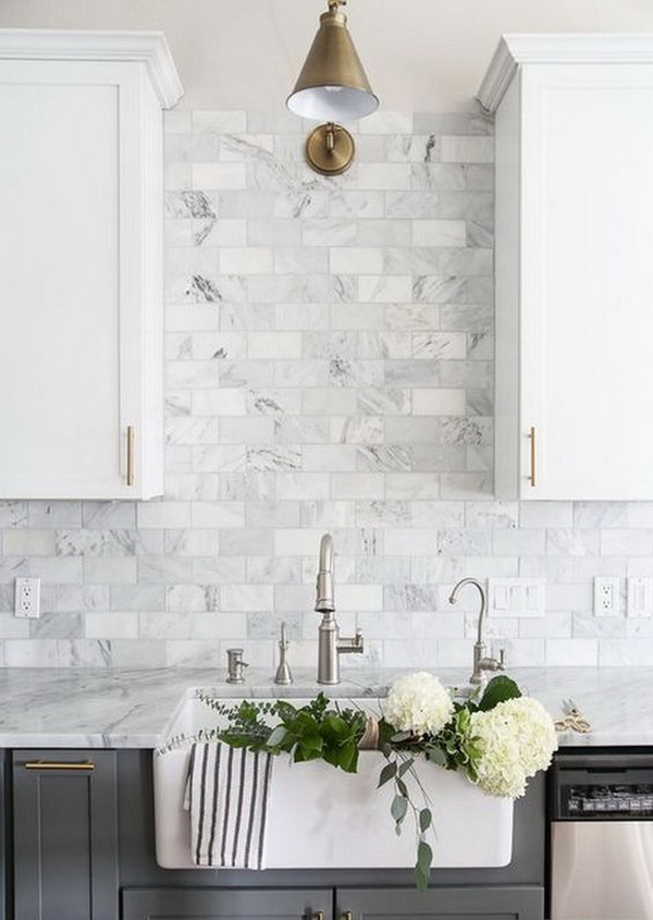Carrara marble subway tile creates a dynamic backdrop for this elegant kitchen. Very clean look with white and light grey color scheme.