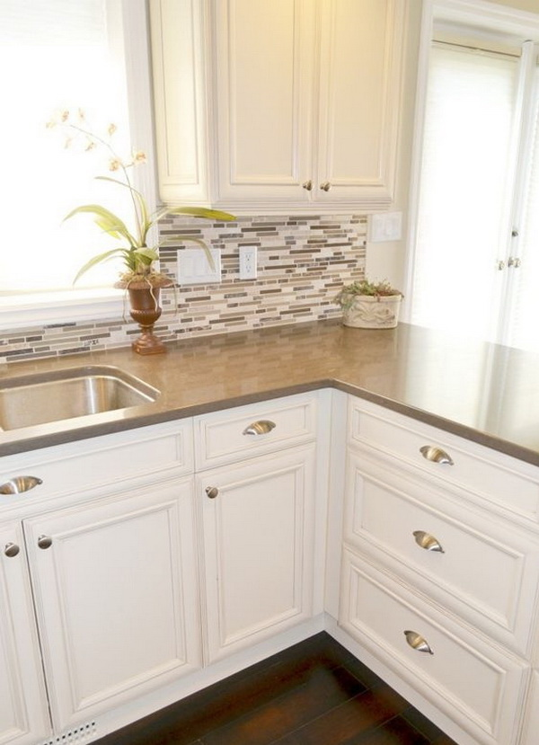 Small mosaic tile backsplash paired with dark wood floors and brown quartz countertops.
