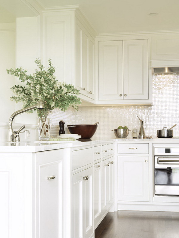 Sparkling and contemporary glass tile backsplash is in harmony with the simple traditional white cabinets.