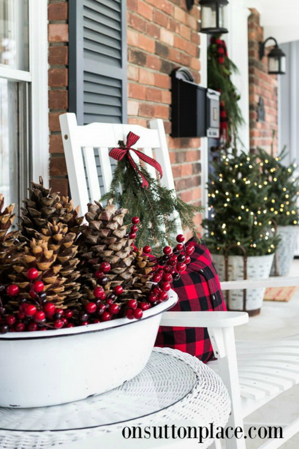 Farmhouse Front Porch Decoration. Decorate your porch with an arrangement of pinecones, winterberries and Buffalo plaid. Lighted live trees and evergreen paired with a throw in reds and blacks will give you the perfect farmhouse front porch.