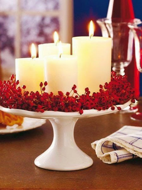 Valentine's Day table decorations. Creating a romantic centerpiece with white candles and dark red berries, great for your family Valentines dinner table!