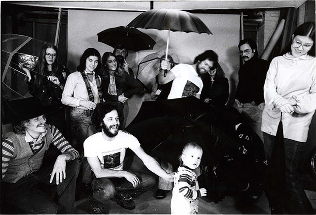 black and white image of Forecast founding group holding up an umbrella