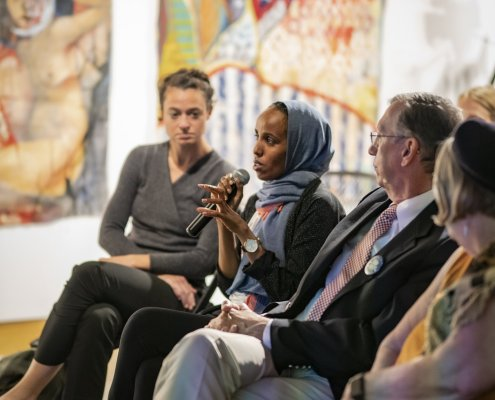 At an event, a Somali woman speaks into a microphone while three other people look on. Large artwork hangs on the wall behind them.