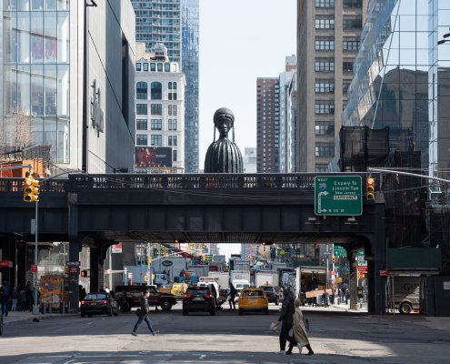 a large-scale black sculpture of a black woman with distinct braids is visible agove a bridge, in the middle of a NYC street.