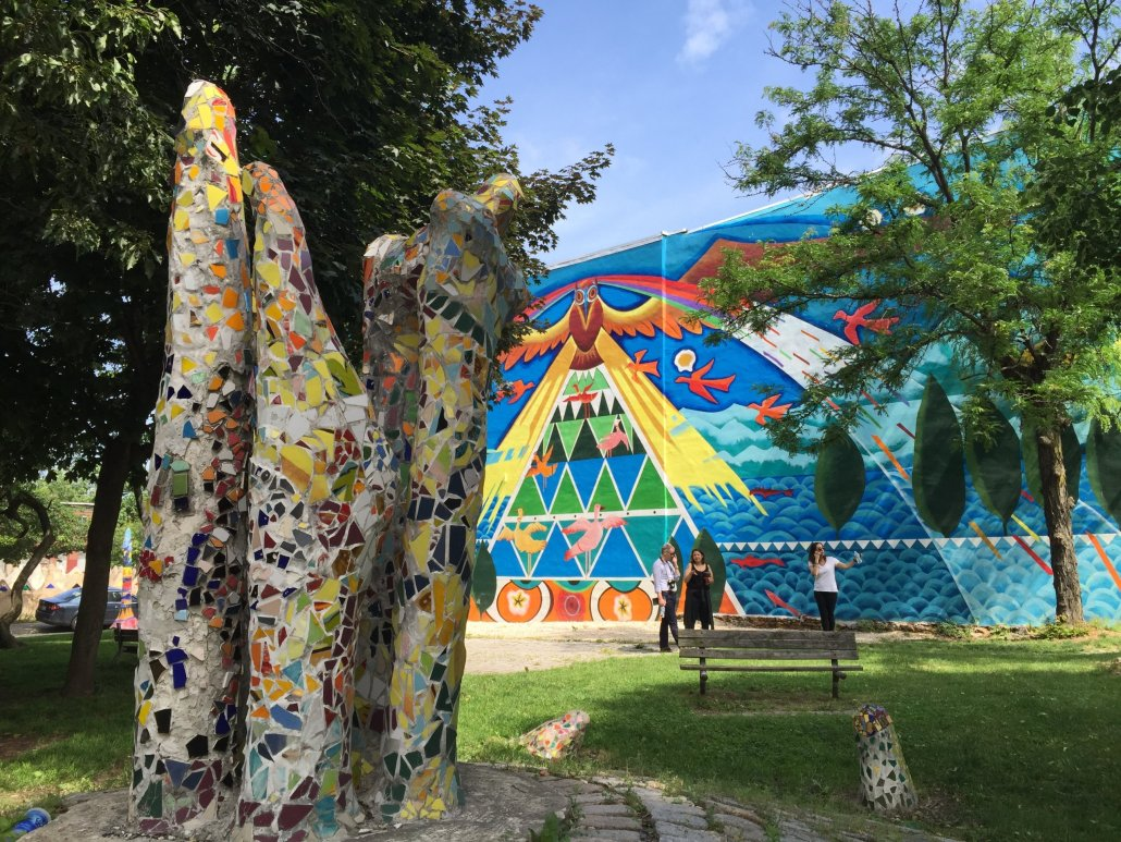 behind a large colorful mosaic form in the foreground, poeple walk in front of a building with a colorful mural