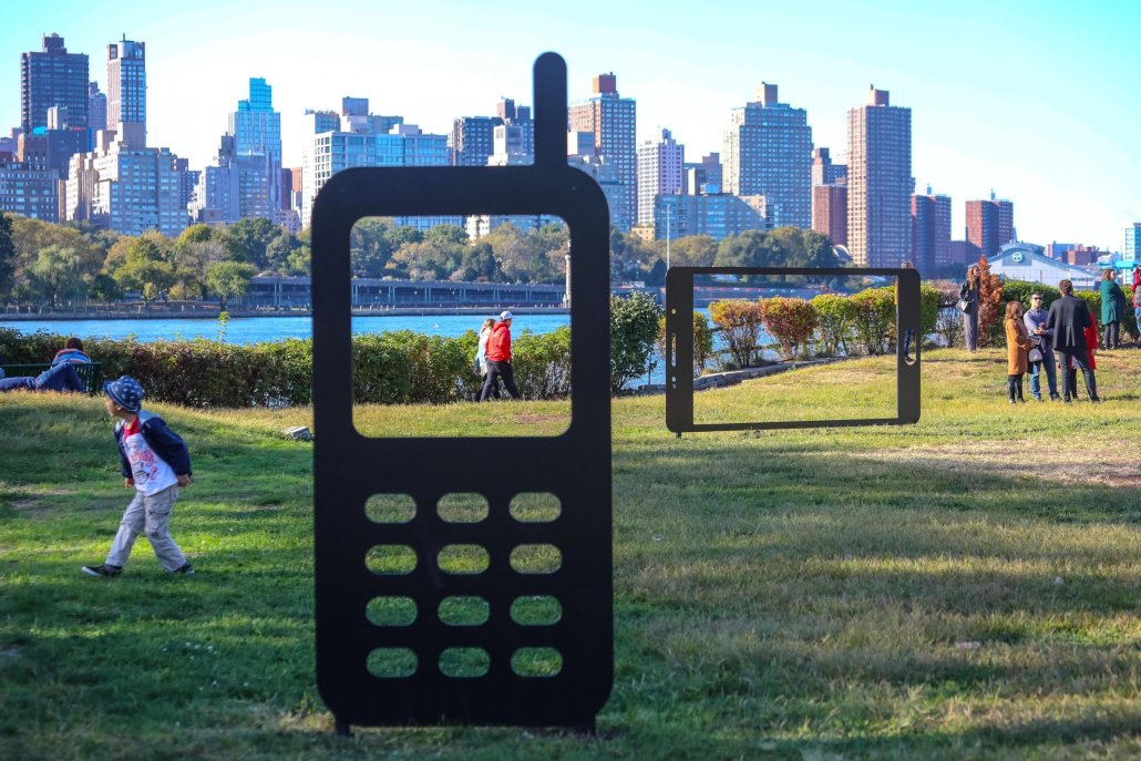 in a green park setting with NYC as a backdrop, two sculptures reference a mobile phone and a tablet; each sculpture has an open frame where the screen would normally appear