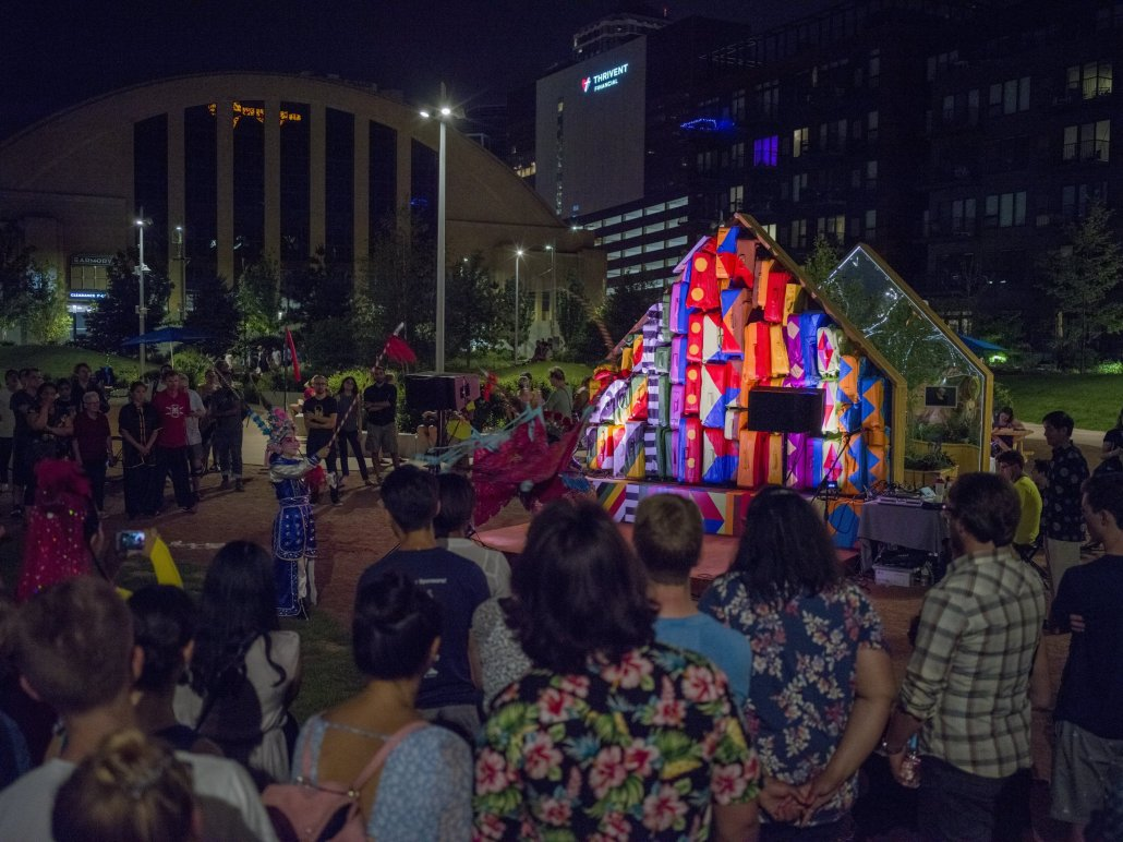 a crowd gathers at night in front of a colorfully lit art installation and stage piece