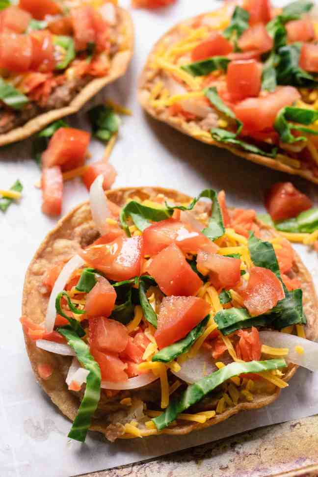 Close up of tostada with cheese, cabbage, and tomatoes