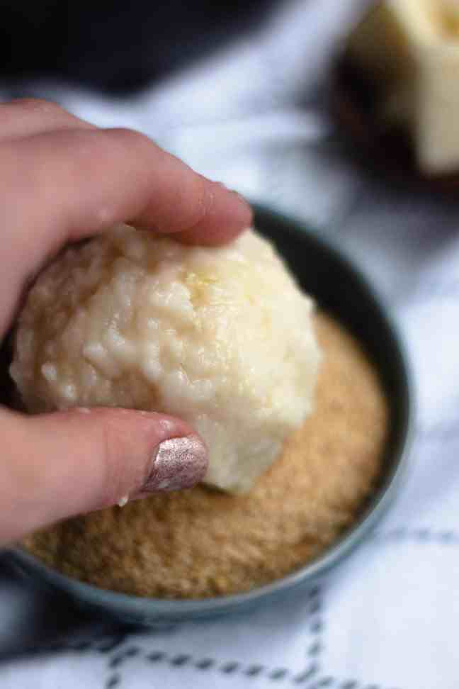 Arancini getting rolled in breadcrumbs