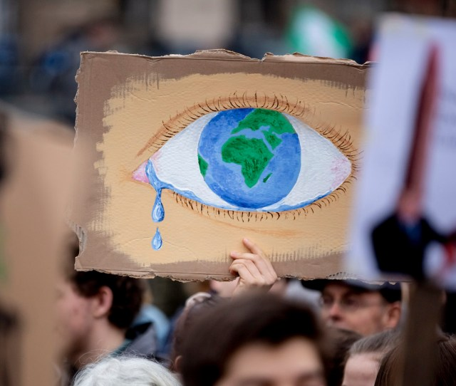 A Protester Holds Up A Poster Depicting The Earth As A Crying Eye During A Demonstration