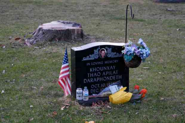 Flowers, drinks, and a flag are left at this grave to commemorate Khounxay Thao Apilat Daraphondeth.