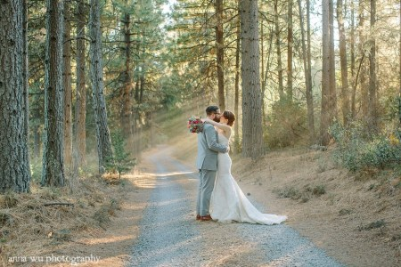 wedding bride and groom kissing in the forest road