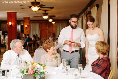 bride and groom talking to parents at wedding reception
