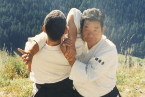 Photo of Morihiro Saito Sensei in the Alps, performing a technique called Katate Dori Kokyu Nage Jodan.