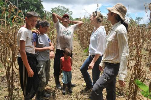 Kaline (direita) falando com família de agricultores no Acre — ficar com as famílias é um dos prazeres do trabalho de campo, diz ela. Kate Evans/CIFOR