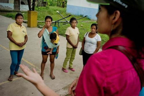 A cientista do CIFOR Elena Mejía, direita, acompanha habitantes quíchuas que estão transportando madeira ao longo do rio Arajuno, no Equador. Tomas Munita/ CIFOR