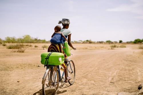 Barry Aliman, 24, va en su bicicleta con su bebé a recoger agua para su familia cerca de Boromo, Burkina Faso. Una nueva herramienta en línea apunta a presentar un panorama claro de cómo los bosques contribuyen a las estrategias de adaptación climática de la población rural. Foto Ollivier Girard/CIFOR.