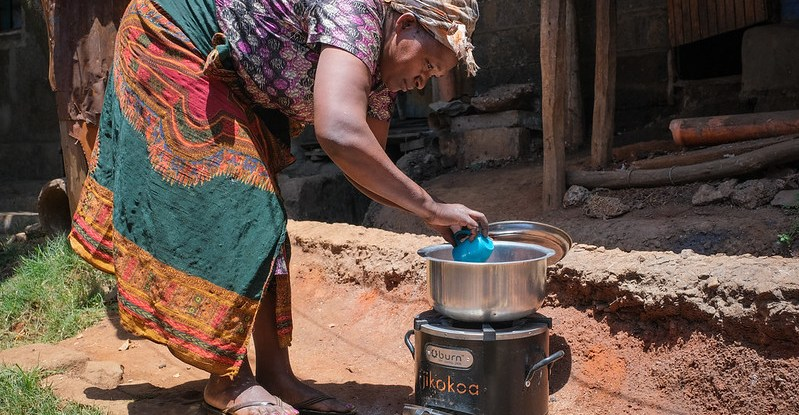 A woman cooks in a pot on an outdoor stove
