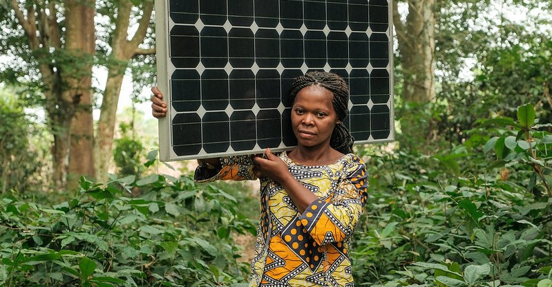 Woman carries a solar panel