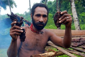 A man holds up bushmeat, Papua, Indonesia. Photo: Agus Andrianto/CIFOR