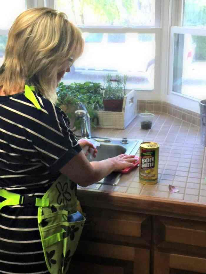 Woman using Bon Ami Powder Cleanser to clean kitchen sink. Effective Nontoxic Cleanser for Spring Cleaning