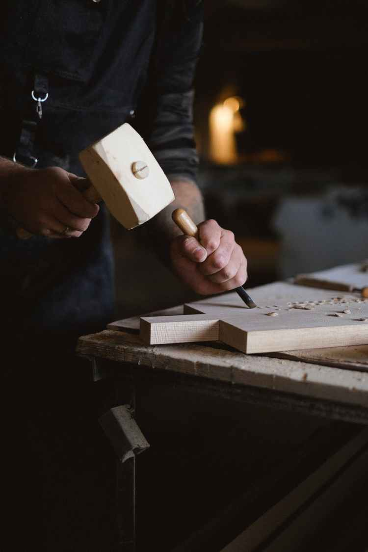 professional craftsman with wood mallet carving piece of wood