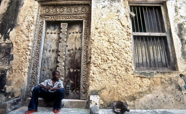 A boy sits in front of a house in Lamu town.
