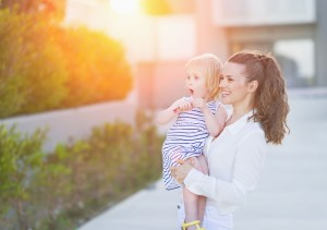 Happy mother and baby in front of house building looking on copy space