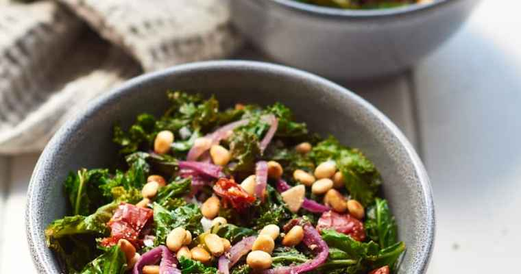 Two bowls of sauteed kale with garlic and pine nuts