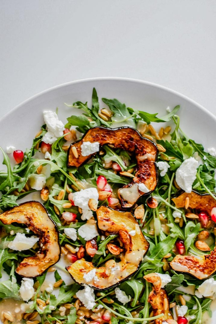4 cups Arugula 2 small or 1 medium winter squash (I used acorn squash) Seeds from 1 pomegranate 1-2 oz goat cheese 1 cup kamut Your favorite dressing (try this or this) 4 slices of bread, toasted (if you're going for a 'salad toast') Salt and pepper to taste